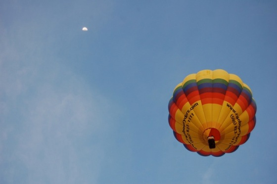 the moon still in the sky as morning balloons take flight at the Balloon Fiesta